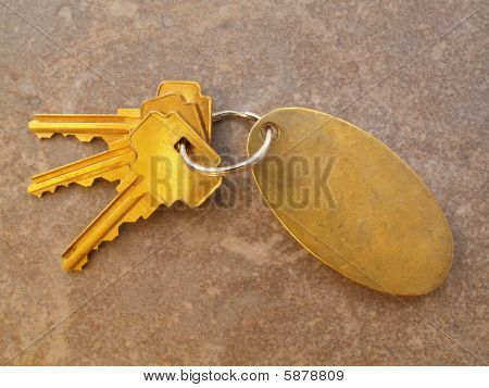 3 Gold Keys And Keychain On Tile