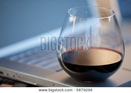 Glass of red wine on laptop