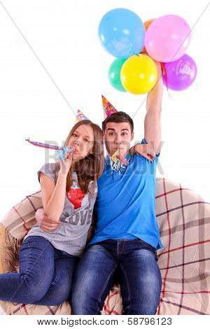 Couple with hats and balloons sitting on the couch