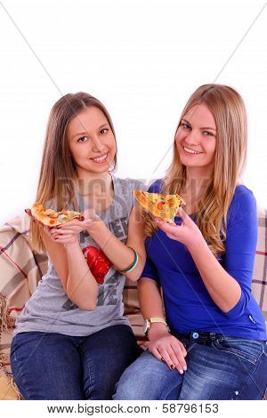 Two Girls Sitting On A Sofa And Eating Pizza