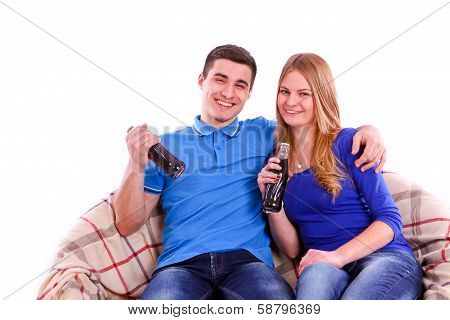 Young People Sitting On A Sofa And Drinking Coca Cola Isolated