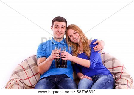 Young Couple Sitting On A Sofa And Drinking Coca Cola Isolated
