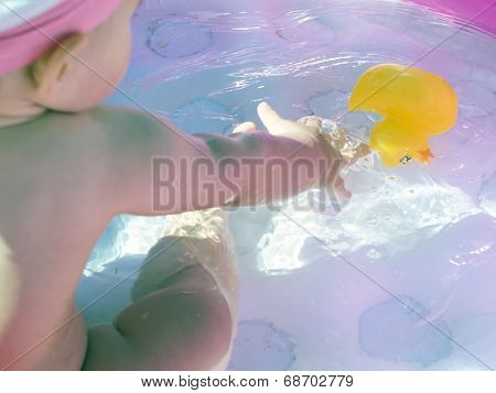 Baby Girl Grabs His Toy Inside An Inflatable Pool On The Beach