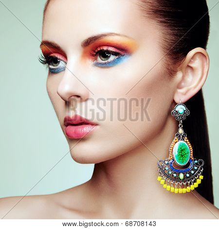 Portrait of beautiful young woman with earring. Jewelry and accessories. Perfect makeup. Fashion photo poster