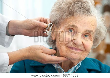 Doctor inserting hearing aid in senior's ear poster