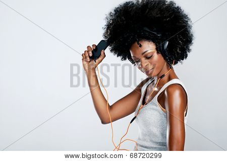 Happy african woman with afro and casual clothing dancing to the music she is listening to from her phone