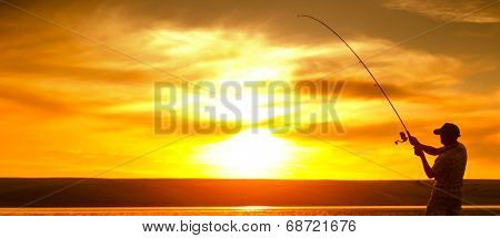 Mature man fishing on the pond at sunset poster