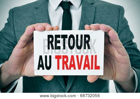 businessman holding a signboard with the text retour au travail, back to work in french, written in it