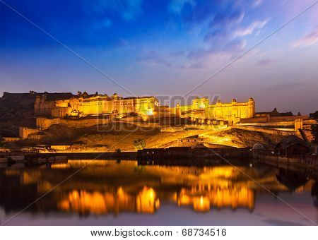 Amer Fort (Amber Fort) illuminated at night - one of principal attractions in Jaipur, Rajastan, India refelcting in Maota lake in twilight