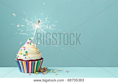 Cupcake decorated with colorful sprinkles and a sparkler