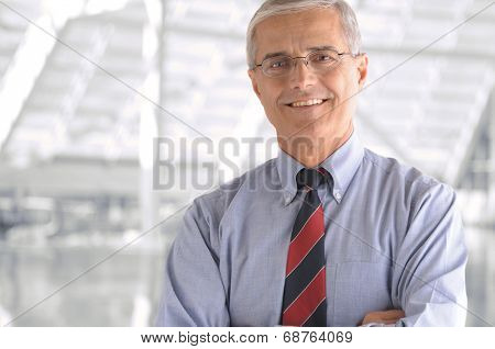Business man portrait in modern office building. Middle aged man is smiling at the camera and has his arms folded. Closeup head and shoulders only.
