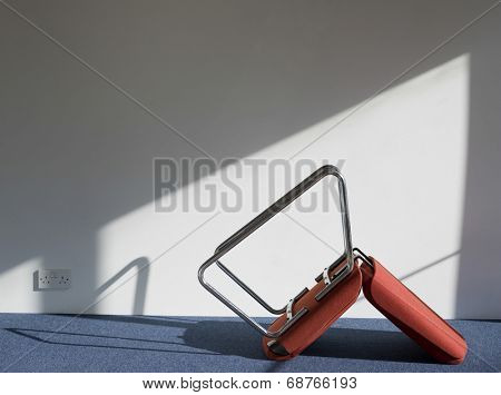 Side view of an upturned office chair casting shadow on wall