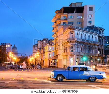 HAVANA,CUBA - JULY 9, 2014 : Urban scene at night in Old Havana with a view of a classic american car and  the street lamps and old buildings near El Prado