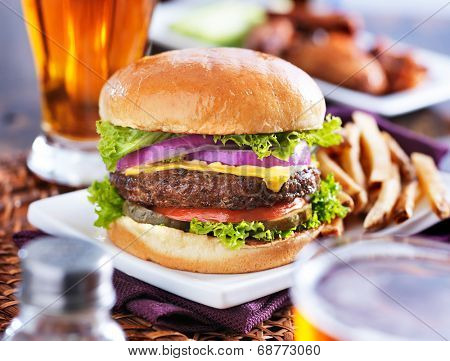 hamburger with fries and beer shot in panorama style with chicken wings in background