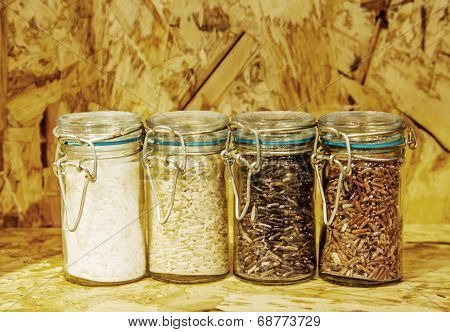 Four Jars Of Rice Varieties In Glass: Brown Rice, Mixed Wild Rice,jasmine Rice,rice Burry On Wood S