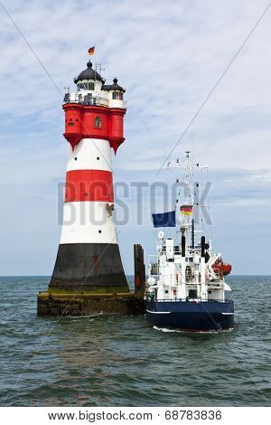 Supply ship moored at lighthouse Roter Sand in the german Wadden Sea
