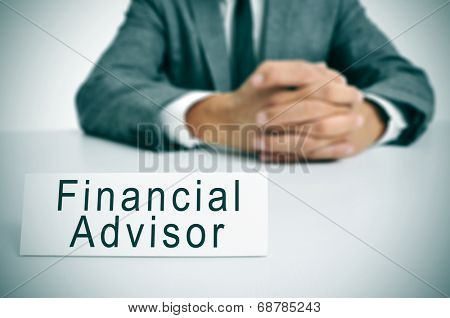 a man wearing a suit sitting in a desk with a signboard in front of him with the text financial advisor written in it