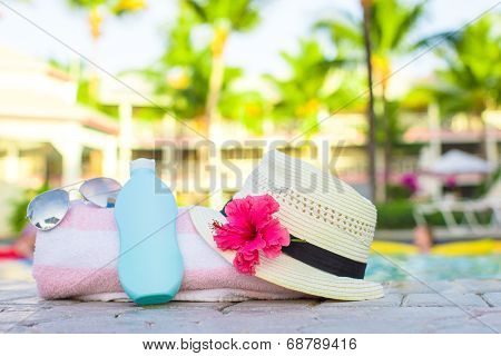 Suncream, hat, sunglasses, flower and tower near pool