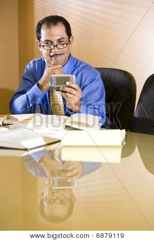 Middle-aged Hispanic businessman reading text message on mobile phone