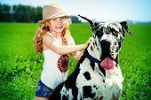 Happy little girl with her mastiff dog on a meadow in summer day. Countryside. poster