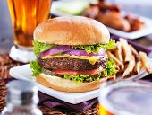 hamburger with fries and beer shot in panorama style with chicken wings in background poster