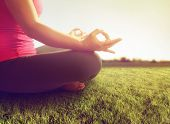 hands of a woman meditating in a yoga pose on the grass toned with a soft sunny filter  poster