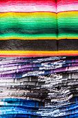 A stack of many colorful woven blankets poster