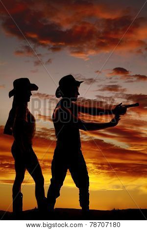 Silhouette Of Cowboy Pointing A Gun With Both Hands