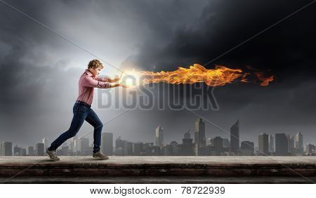 Young man in casual throwing magic fire balls