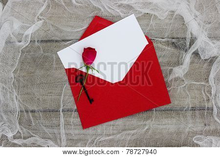 Blank white letter and rose in red envelope with key on shabby background