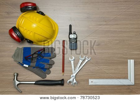 Background with various personal safety accessories and assorted tools on a wooden surface. Items include a hard hat with ear protection attached, safety goggles, working gloves and a cb radio
