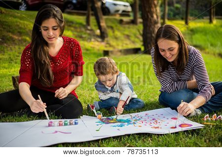 Happy Mother Aunt Sister And Son Child Painting In The Park