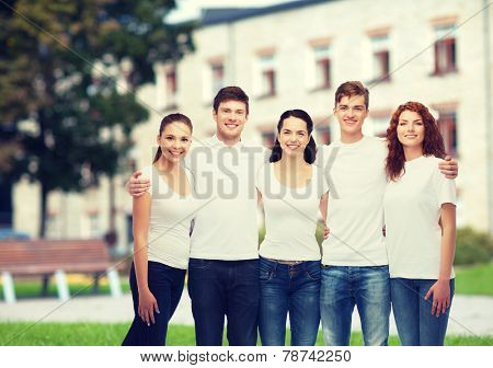advertising, friendship, education, scool and people concept - group of smiling teenagers in white blank t-shirts over campus background poster