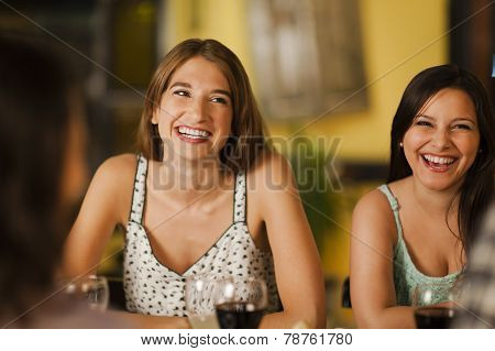 Two Young Women Laughting In A Restaurant