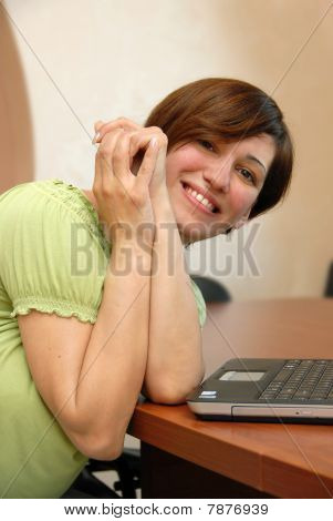 Smiling Woman At The Office Desk