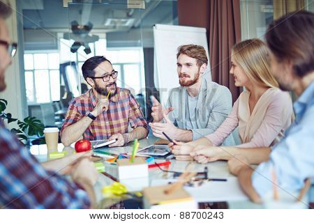 Business team looking at young man talking about new tendencies