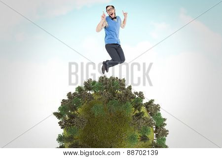 Geeky hipster jumping and smiling against blue sky