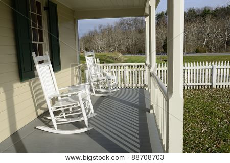 White Rocking Chairs on Front Porch with Picket Fence