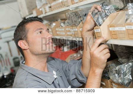 Man choosing parts from stores