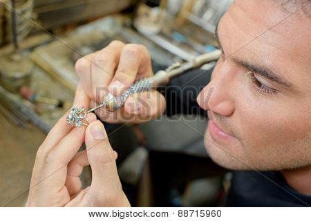 Skilled jeweller repairing a ring