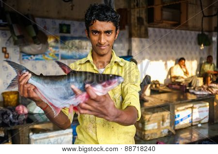 MUMBAI, INDIA - 08 JANUARY 2015: Worker on a fishmarket next to Dhobi ghat showing a fish while waiting for customers.