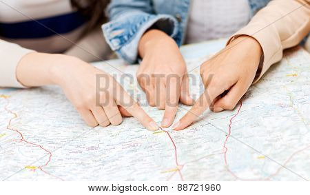 holidays and tourism concept - friends with tourist map in the city