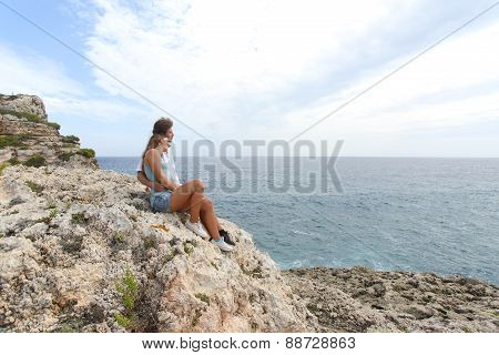Teenager couple hugging and looking at horizon on a cliff poster