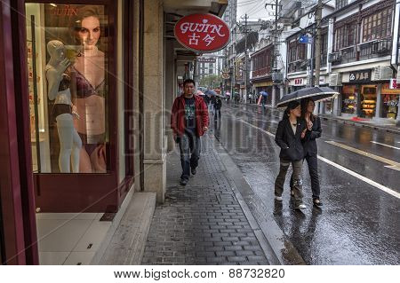 Passers Flow Along Wet Pavementwalked Past Store On City Street.