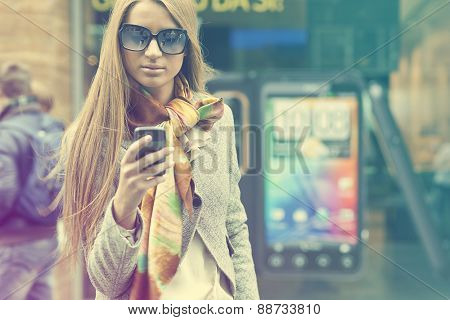 Young Woman with smartphone walking on street, downtown. In background is blured street