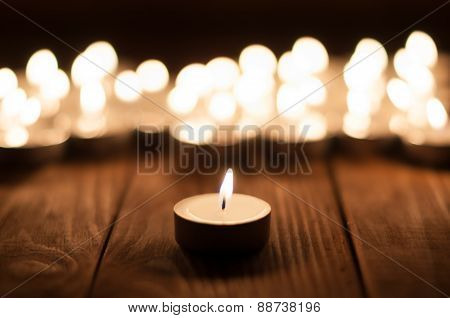 One candle and blurry candles on old wooden background