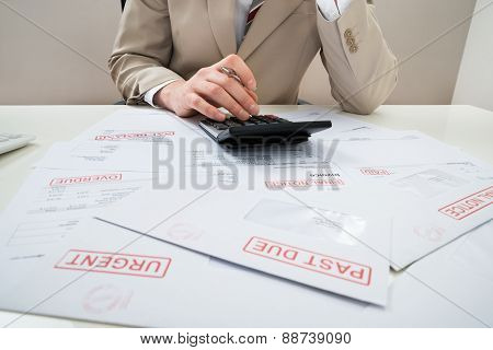 Businessman With Calculator And Unpaid Bills