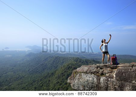 young woman hiker taking photo with  digital camera at mountain peak