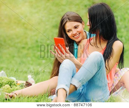 Two Women Friends Laughing And Sharing Pictures In A Smart Phone On Picnic At The Park