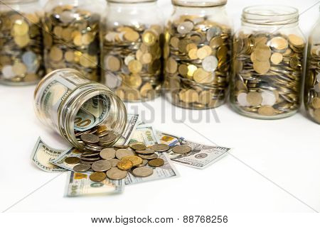Horizontal shot of coins spilling from coin jar